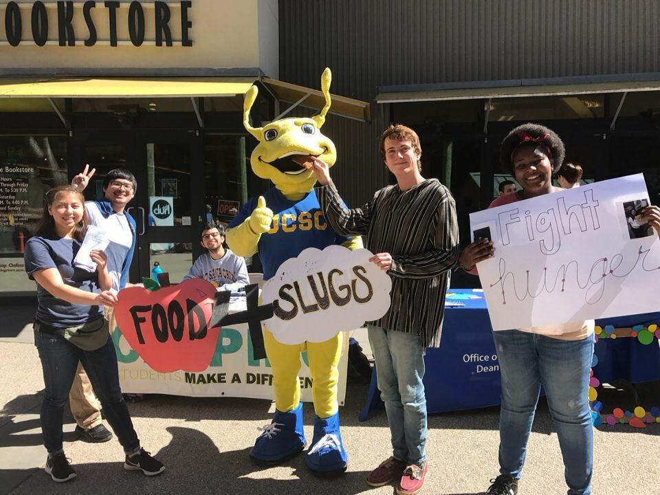 people holding food4slugs sign with slug mascot behind it